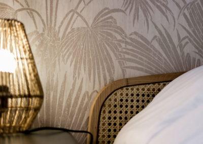 Tapisserie, angle de lit et luminaire design sur une table de nuit