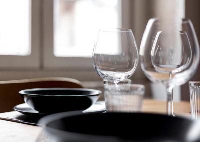 table et déco design, verres à pied, assiettes noires et verre à eau
