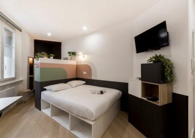 Salon avec télé, plante verte, lit, plancher en bois