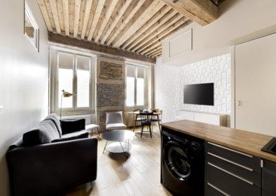 Vue d'un salon avec canapé, cuisine design à droite, table basse, table design, deux fenêtre, télé écran plat accrochée au mûr