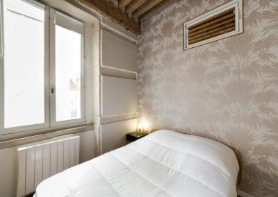lit, couverture blanche, tapisserie et plafond poutres en bois