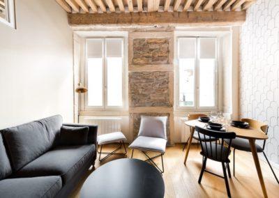 pièce à vivre, canapé, table basse, table à manger, fauteuil, mûr en pierre, plafond avec poutres en bois, deux fenêtre, déco design